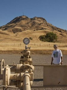 Dave Garcia, who has led the fight against fracking in Butte County, poses near a gas-well pump in the nearby Sutter Buttes, where many wells have undergone hydraulic fracturing.